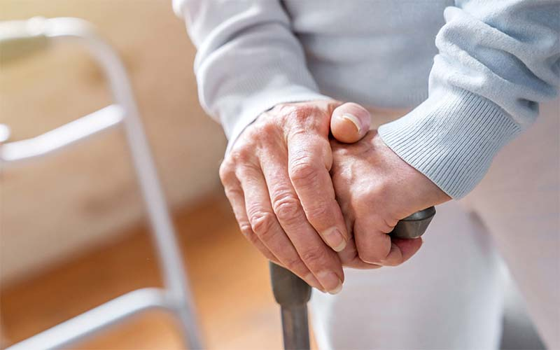 An older person's hands rest on top of a cane, with a view of a walker behind them